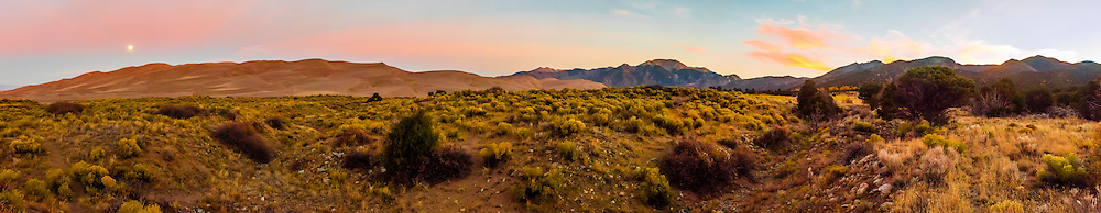 Panoramic view of the full moon about to set over Great Sand Dunes National Park and Preserve, near Mosca, Colorado USA.