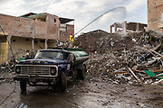 2016/08/05 – Portoviejo, Ecuador: A man waters debris in Portoviejo, Ecuador, in order to settle down the dust from the buildings collapsed by the earthquake, 5th August 2016.<br /> Portoviejo's town centre is closed to the public and secured by the army since most of its building were heavily damaged by the earthquake, turning it into a ground zero area. (Eduardo Leal)