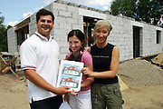 (MODEL RELEASED IMAGE). Hubert Sobczynski, his daughter Klaudia, and his wife Marzena at the construction site of their new house hold a picture of the final design. (Supporting image from the project Hungry Planet: What the World Eats.)