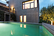 external of a modern house with pool, night scene