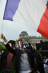 May 7, 2017 - Paris, Ile-de-France, France - A Macron supporter waves a French flag and has his face painted with a French and EU flag. Emmanuel Macron, the winner of the 2017 French Presidential election from the political movement En Marche!, addressed his supporters at the square outside the Louvre Museum after it became clear that he won the second round of the election against Marine Le Pen from the Front National. (Credit Image: © Michael Debets/Pacific Press via ZUMA Wire)