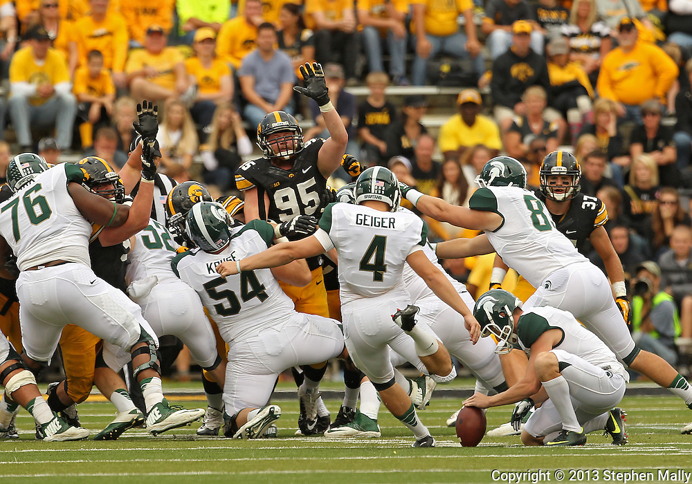 October 6 2013: Michigan State Spartans kicker Michael Geiger (4) kicks a field goal from the hold of Michigan State Spartans punter Mike Sadler (3) during the second half of the NCAA football game between the Michigan State Spartans and the Iowa Hawkeyes at Kinnick Stadium in Iowa City, Iowa on October 6, 2013. Michigan State defeated Iowa 26-14.