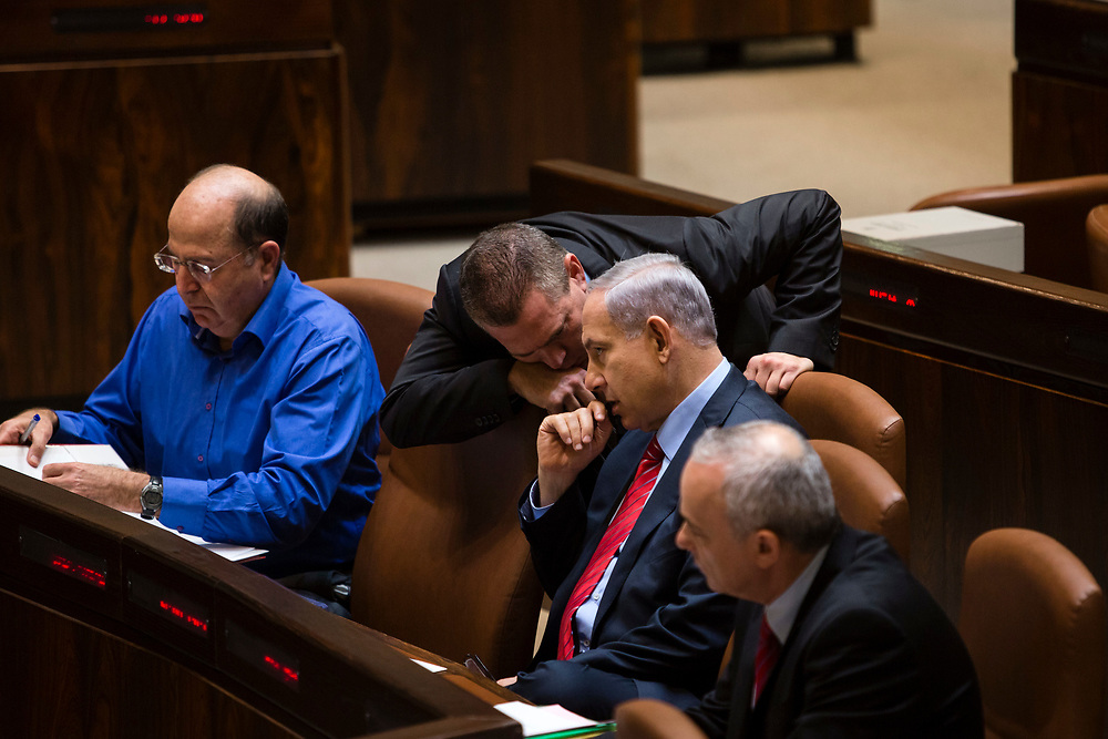 Israeli Prime Minister Benjamin Netanyahu (2nd R) speaks with ministers at the Knesset, Israel's parliament in Jerusalem, on December 3, 2014, during the vote to dissolve the parliament. Israeli legislators voted Wednesday to dissolve the parliament, and they set March 17 as the date for parliamentary elections, two years ahead of schedule, following a crisis within Prime Minister Netanyahu's coalition government.