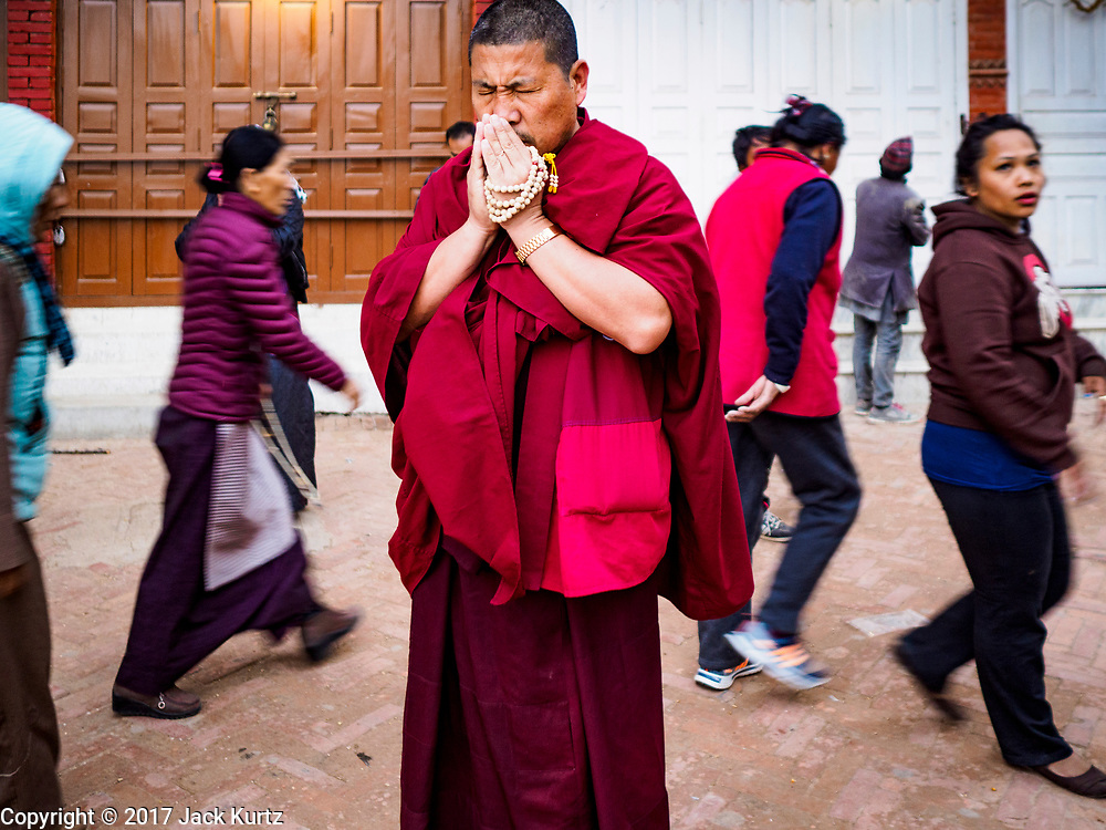 17 MARCH 2017 - KATHMANDU, NEPAL: A monk faces Boudhanath Stupa and prays during morning processions around the stupe in Kathmandu. It is the holiest site in Nepali Buddhism. It is also the center of the Tibetan exile community in Kathmandu. The Stupa was badly damaged in the 2015 earthquake but was one of the first buildings renovated.     PHOTO BY JACK KURTZ