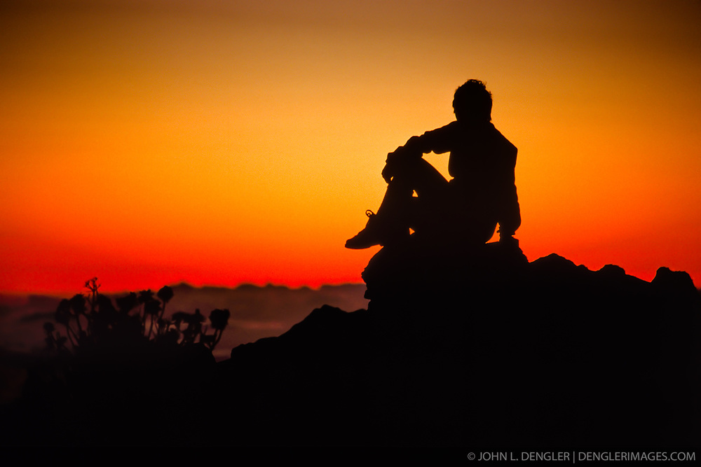 Spectacular sunsets and sunrises attract tourists to the summit area of Haleakalā National Park on the island of Maui, Hawaii. In this photo a hiker watches the fading twilight sunlight after sunset near, Pu'u'ula'ula (Red Hill), the highest point on Maui (10,023 ft.). The 33,265 acre park consists of the Summit District and the coastal Kipahulu District. Haleakalā National Park is known for it volcanic features, cinder cones and clear night skies for star gazing. The Haleakalā Volcano of east Maui is considered dormant, having last erupted sometime between 1480 and 1600 AD.