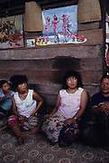 DAYAK, MALAYSIA. Sarawak, Borneo, South East Asia.Dayak women sitting inside longhouse. Poster shows western ideal as opposed to their own physique. Tropical rainforest and one of the world's richest, oldest eco-systems, flora and fauna, under threat from development, logging and deforestation. Home to indigenous Dayak native tribal peoples, farming by slash and burn cultivation, fishing and hunting wild boar. Home to the Penan, traditional nomadic hunter-gatherers, of whom only one thousand survive, eating roots, and hunting wild animals with blowpipes. Animists, Christians, they still practice traditional medicine from herbs and plants. Native people have mounted protests and blockades against logging concessions, many have been arrested and imprisoned.