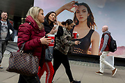 Three shopping girlfriends walk past a billboard ad featuring the face of a model advertising a perfume outside the retailer Debenhams on Oxford Street, on 16th April 2018, in London, England.
