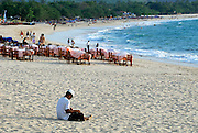 Local Balinese man sitting on sand of Jimbaran Bay, tables and chairs of beachside restaurant in background. Jimbaran Bay was the location of the second Bali terrorist bombing on October 2, 2005. Jimbaran Bay, Bali, Indonesia.