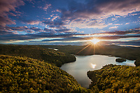 Sunset with sunstar over the green mountains and Nichol's Pond, from Nichol's Ledge in Cabot, Vermont