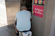 Large gentleman sitting outside a Belgian Waffle kiosk on 26th June 2020 in London, United Kingdom. In North America, Belgian waffles are a variety of waffle with a lighter batter, larger squares, and deeper pockets than ordinary American waffles. Belgian waffles were originally leavened with yeast, but baking powder is now often used. They are often eaten as a breakfast food or as a dessert. These waffles are seen as a fat and sugar filled food which eaten in excess is not good for overall health.
