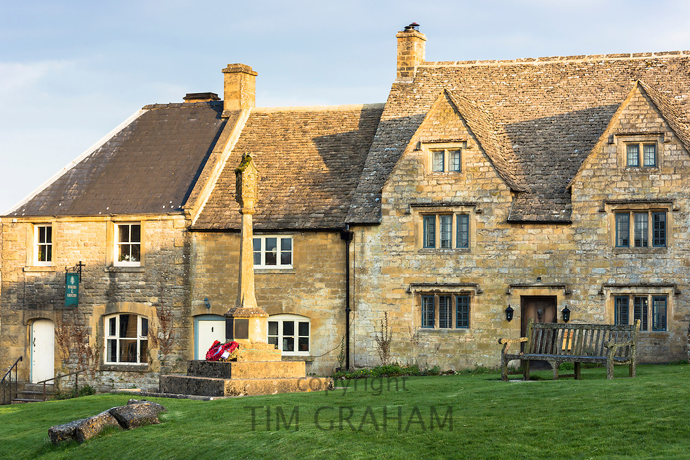 War Memorial with commemorative poppies, quaint cottages, shop and leaded light windows in Temple Guiting, The Cotswolds, UK