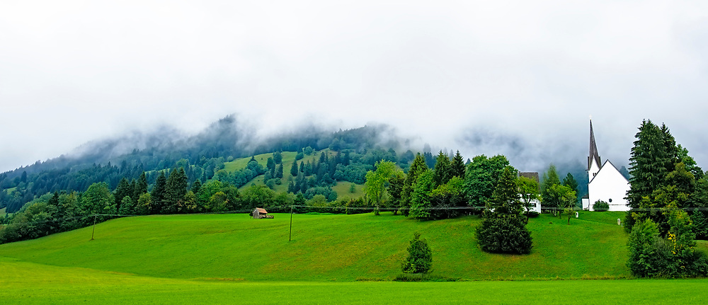 White church against a backdrop of the Bavarian Alps just outside of Oberammergau in Germany