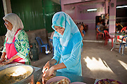 """Sept. 24, 2009 -- PATTANI, THAILAND:  Muslim women make roti, a traditional Malaysian flat bread, in a tea shop in central Pattani, Thailand. Thailand's three southern most provinces; Yala, Pattani and Narathiwat are often called """"restive"""" and a decades long Muslim insurgency has gained traction recently. Nearly 4,000 people have been killed since 2004. The three southern provinces are under emergency control and there are more than 60,000 Thai military, police and paramilitary militia forces trying to keep the peace battling insurgents who favor car bombs and assassination.   Photo by Jack Kurtz"""