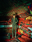 At 19, Effendi Boi's youngest son, Raheem-u-din, is already addicted to opium like his father. Here  standing in his yurt, wearing his tight chinese suit. A family usually owns about 40 blankets, displayed in the yurt. At Effendi Boi's summer camp of Aq Jilga.<br /> <br /> Adventure through the Afghan Pamir mountains, among the Afghan Kyrgyz and into Pakistan's Karakoram mountains. July/August 2005. Afghanistan / Pakistan.