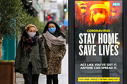 """© Licensed to London News Pictures. 12/01/2021. London, UK. Women wearing protective face coverings walk past the government's 'Stay Home, Save Lives' Covid-19 publicity campaign poster in north London, as the number of cases of the mutated variant of the SARS-Cov-2 virus continues to spread around the country. The message in the advertising campaign asks people to act like they have Covid and Prime Minister Boris Johnson has said that the public should """"stay at home"""". Photo credit: Dinendra Haria/LNP"""