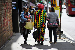 © Licensed to London News Pictures. 24/08/2018. London, UK. A man in Rastafarian colours is greeted as he walks down Ladbroke Grove in Notting Hill, West London ahead of the 2018 Notting Hill Carnival which starts this weekend. Photo credit: Ben Cawthra/LNP