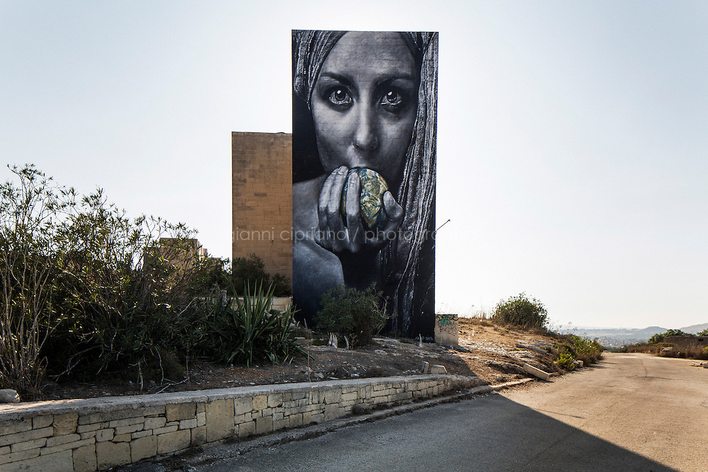 """PEMBROKE, MALTA - 28 AUGUST 2016: Graffitis by street artis """"Clap"""", depicting a woman holding the world in her hands, is seen here on the the wall of an abandoned building of the White Rocks Complex in Pembroke, Malta, on August 28th 2016.<br /> <br /> The White Rocks area was originally developed as quarters for the British services. When the British left, the area was turned into a tourist complex but it eventually closed down and fell into ruins.<br /> <br /> While many cities across the world denounce the defacing of a public property, on the Mediterranean island of Malta it is encouraged.<br /> <br /> According to Sandra Borg of Arts Council Malta, street art projects """"engage with numerous communities and contribute directly to urban regeneration"""". Funding from Arts Council Malta, allows schools to offer additional creative arts subjects and many choose street art; with 'NO WAR' creator, James Grimaud, teaching students sketching, stencil making and aerosol use."""