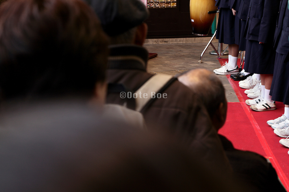 group of school children lined up on a red carpet Japan