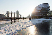 People walk to work on the south bank in front of Tower Bridge and City Hall after snow has fallen overnight in London, England on February 28th, 2018. Freezing weather conditions dubbed the Beast from the East have brought snow and sub-zero temperatures to the UK.