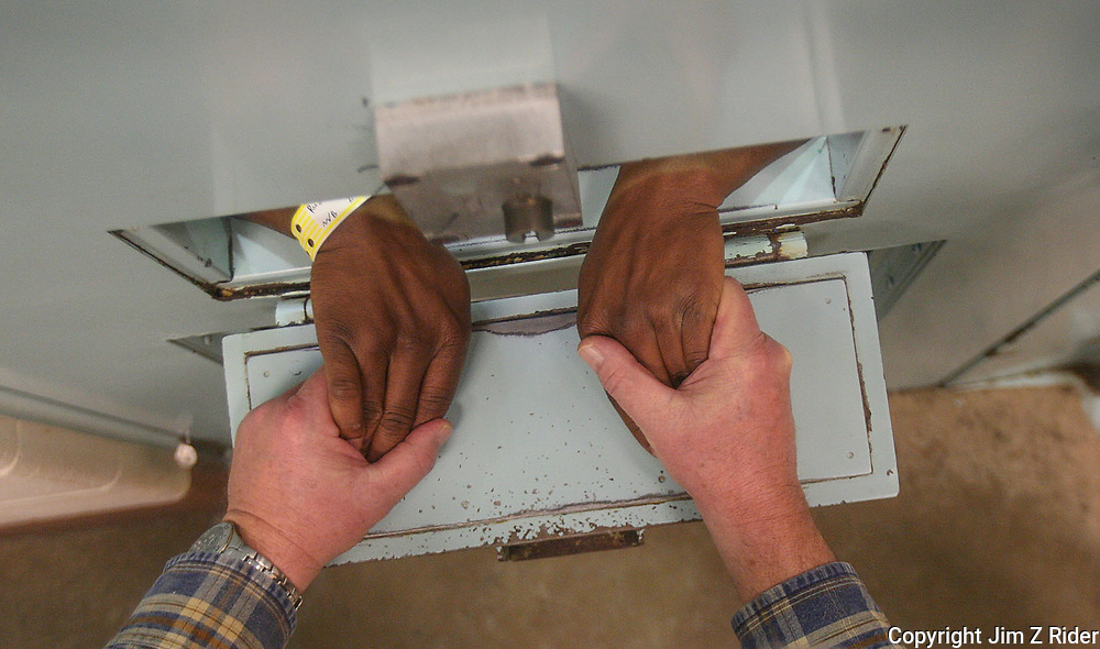 Chaplain Coyle prays with a prisoner through the jail cell door slot.