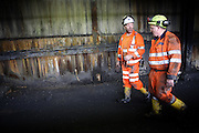 Peter Hunter, (left) and Tony Roberts, (right), the general manager of Unity Mine and lifelong miner are walking in a passage linking Unity main complex to the entrance of the mine to check the ongoing restoring operations, on Wednesday, Apr. 11, 2007, in Cwmgwrach, Vale of Neath, South Wales. The time is ripe again for an unexpected revival of the coal industry in the Vale of Neath due to the increasing prize and diminishing reserves of oil and gas, the uncertainties of renewable energy sources, and the technological advancement in producing energy from coal while limiting emissions of pollutants, has created the basis for valuable investment opportunities and a possible alternative to the latest energy crisis. Unity Mine, in particular, has started a pioneering effort to revive the coal industry in the area, reopening after more than 8 years with the intent of exploiting the large resources still buried underground. Coal could be then answer to both, access to cheaper and paradoxically greener energy and a better and safer choice than nuclear energy as a major supply for the decades to come. It is estimated that coal reserves in Wales amount to over 250 million tonnes, or the equivalent of at least 50 years of energy supply, while the worldwide total coal could last for over 200 years as a viable resource compared to only a few decades of oil and natural gas.