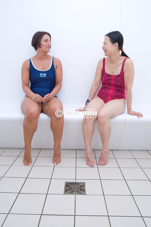 Two women relaxing in the steam room at their sports leisure centre,