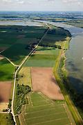 Nederland, Brabant, Gemeente Werkendam, 12-06-2009; polder Noordwaard in de Biesbosch, onderdeel van 'Ruimte voor de Rivier' (bescherming tegen hoogwater door rivierverruiming). Door het gedeeltelijke afgraven van de dijken zijn in- en uitstroomopeningen in de Merwededijk gemaakt (boven in beeld) en is een doorstroomgebied ontstaan waardoor de kans op overstromingen (in de bovenloop) kleiner is. Het deel van de polder wat nu nog landbouwgrond is, onder in beeld, zal in de toekomst ook ontpoldert worden..Polder Noordwaard (part of Biesbosch National Park), part of the program 'Space for the River' (protection against high water by means of creating space for rivers)..Because the dike next to the river has been partly excavated, entrances for the water of the river have been made (left, above middle). The former polder left of the dike can now store water and allows the river to flood more easily downstream (direction of the Northsea). These mesures dimishes the risk of floods further upstream at high water in the winter. The remaining polder (below) will be 'depoldered' in the future. ).Swart collectie, luchtfoto (25 procent toeslag); Swart Collection, aerial photo (additional fee required).foto Siebe Swart / photo Siebe Swart