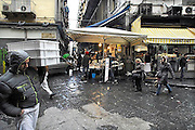 Italie, Napels, 7-3-2008Een van de karakteristieke nauwe straatjes in het oude centrum. Groentewinkel. De stad weet met zijn afval geen raad meer en in het hele gebied liggen illegale hopen afval. Een nieuwe vuilverbrandingsoven is pas in 2009 bedrijfsklaar. Tot die tijd heeft de maffia, camorra grote invloed op de afvalverwerking van deze stad.Industrieel afval en huishoudelijk afval veroorzaken grote water en bodemvervuiling, terwijl de streek een belangrijk tuinbouwgebied is.Foto: Flip Franssen