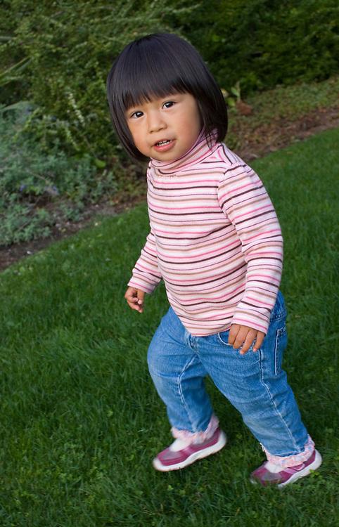 United States, Washington, Bellevue, Girl (age 2) walking on grass.  MR