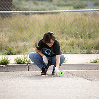 Detective Tasheena Wilson with Gallup Police Department collects evidence on Kachina Street behind Wal-Mart as she investigates a stabbing that took place in the area, Wednesday, June 5 in Gallup.