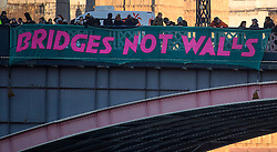 © Licensed to London News Pictures. 20/01/2017. London, UK.  As part of the 'Bridges not Walls' campaign of national demonstrations against Donald Trump, a banner is suspended from Lambeth Bridge in London showing the Houses of Parliamnet. Donald Trump will attend his inauguration ceremony in Washington later today. Photo credit: Ben Cawthra/LNP