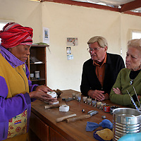 Africa, Namibia, Windhoek. A Namibian woman at Penduka demonstrates bead making from recycled glass bottles to visitors.