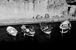 Porto nella Marina di Novaglie. Si notano quattro le barche dei pescatori, di colore prevalentemente bianco e blu, parcheggiate. Il porto è scavato nella scogliera come capita di trovare in molte marine salentine.