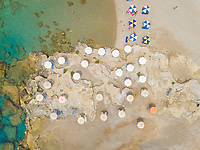 Aerial view of blue and white parasols on the shores of Rhodes island, Greece.