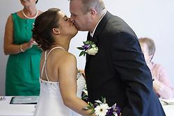 Bride who has cerebral palsy, kissing groom at wedding ceremony.