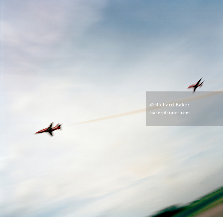 The Hawk jets of the 'Red Arrows', Britain's Royal Air Force aerobatic team make a low-level pass through summer skies.