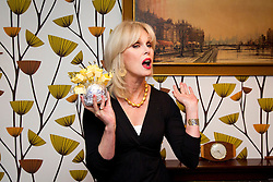 © Licensed to London News Pictures. 27/09/2012. LONDON, UK. Actress Joanna Lumley is seen in a recreated 70's sitting room holding a typical 70's party snack, pineapple and cheese on sticks, at the launch of YouView in London today (27/09/12). YouView, launched today by broad band provider TalkTalk, provides on demand television for its customers who will be given the set-top boxes for free. Photo credit: Matt Cetti-Roberts/LNP