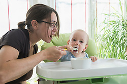 Mother feeding baby food to her baby boy with spoon, Munich, Bavaria, Germany