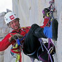 Alex Lowe looks for gear to use on a very difficult aid climbing pitch, high up Great Sail Peak on Canada's Baffin Island.