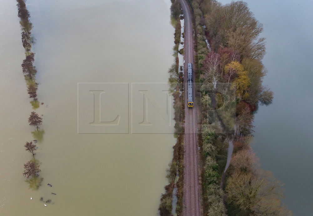 © Licensed to London News Pictures. 04/02/2021. Little Marlow, UK. A train makes its way along the track surrounded River Thames floodwater (L) and a lake - near Little Marlow in Buckinghamshire. Large parts of the UK have experienced more wet conditions bringing further flooding . Photo credit: Peter Macdiarmid/LNP