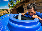 02 JUNE 2016 - SIEM REAP, CAMBODIA: NGOR, 33 years old, checks the lever of the water in the 3,000 litre water tank on his tractor. He sells water from his well in the villages around his home east of Siem Reap. Cambodia is in the second year of  a record shattering drought, brought on by climate change and the El Niño weather pattern. Farmers in the area say this is driest they have ever seen their fields. They said they are planting because they have no choice but if they rainy season doesn't come, or if it's like last year's very short rainy season they will lose their crops. Many of the wells in the area have run dry and people are being forced to buy water to meet their domestic needs.      PHOTO BY JACK KURTZ