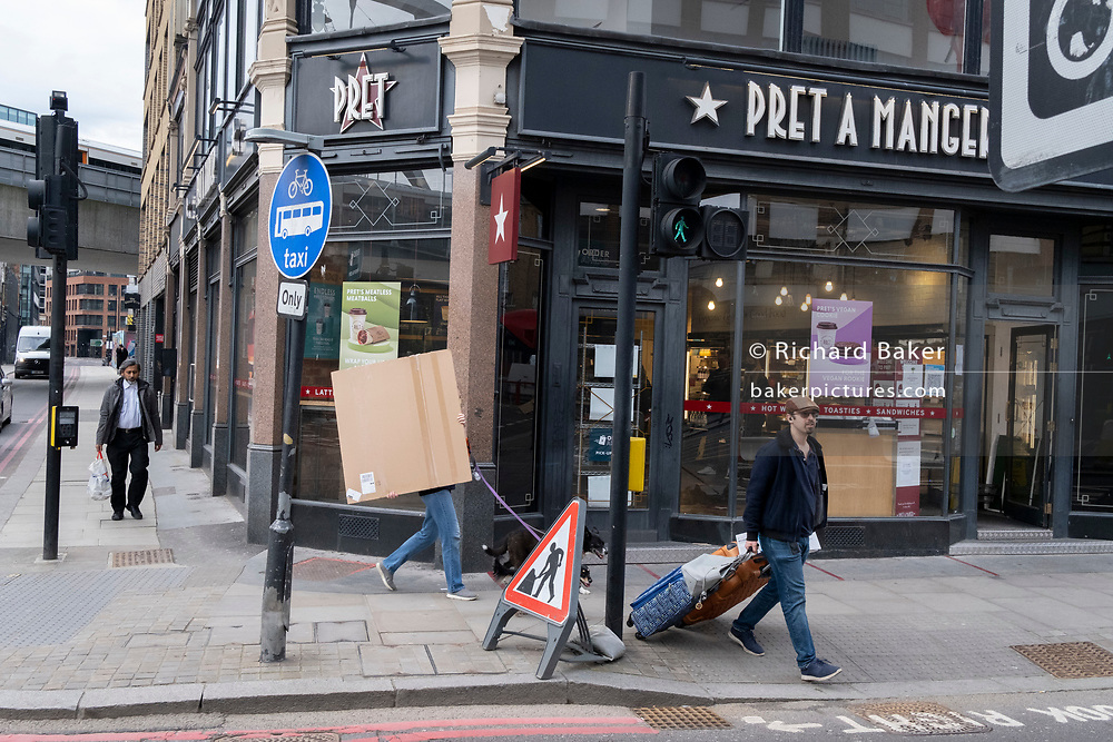 A pedestrian walking two dogs is about to carry a wrapped square item across the road in Hoxton, on 24th February 2021, in London, England.