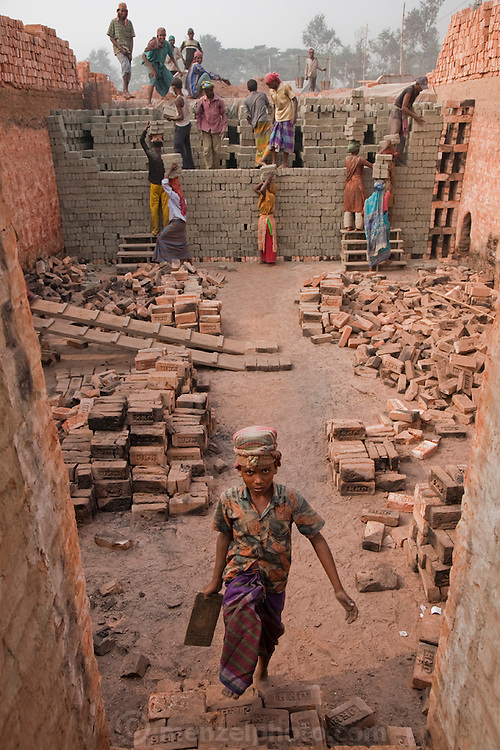 A boy prepares to carry his next load of bricks at the JRB brick factory near Sonargaon, outside Dhaka, Bangladesh. The heavy clay soils along the river near the market town of Sonargaon are well suited for making bricks. At the JRB brick factory, workers of all ages move raw bricks from long, stacked rows, where they first dry in the sun, to the smoky coal-fired kilns. After being fired, the bricks turn red. A foreman keeps tally, handing the workers colored plastic tokens corresponding to the number of bricks they carry past him. They cash in the chips at the end of each shift, taking home the equivalent of $2 to $4 (USD) a day.