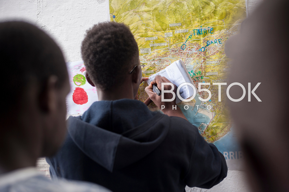 An African migrant writes on his notebook the way to cross the border. September 4, 2018. A group of voluntiers have created a hosting network for migrants in transit who have already completed the 5-day period that can remain in public resources. This group of volunteers is avoiding a serious humanitarian problem Irún, the Basque municipality on the border with Hendaye. As the number of migrants arriving on the coasts of southern Spain incresead, more and more migrants are heading north to the border city of Irun. (Gari Garaialde / Bostok Photo)