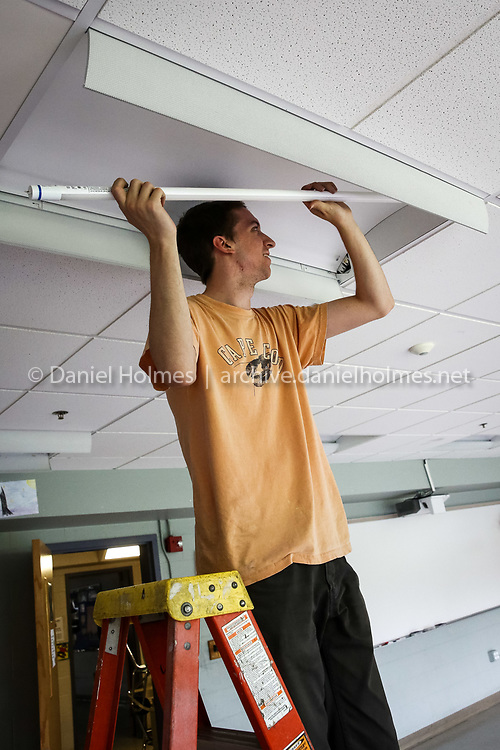 (6/25/15, HOLLISTON, MA) Tom Denman installs new energy-efficient LED bulbs in a classroom at Holliston High School on Thursday. Daily News and Wicked Local Photo/Dan Holmes