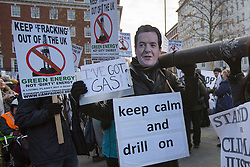 © licensed to London News Pictures. London, UK 01/12/2012. A protester wearing a George Osborne mask helping to building a 200 metre ?oil pipeline? from the Canadian High Commission to the US Embassy in Grosvenor Square to protest against the Keystone XL pipeline being built to transport Canadian Tar Sands oil to the US. Photo credit: Tolga Akmen/LNP