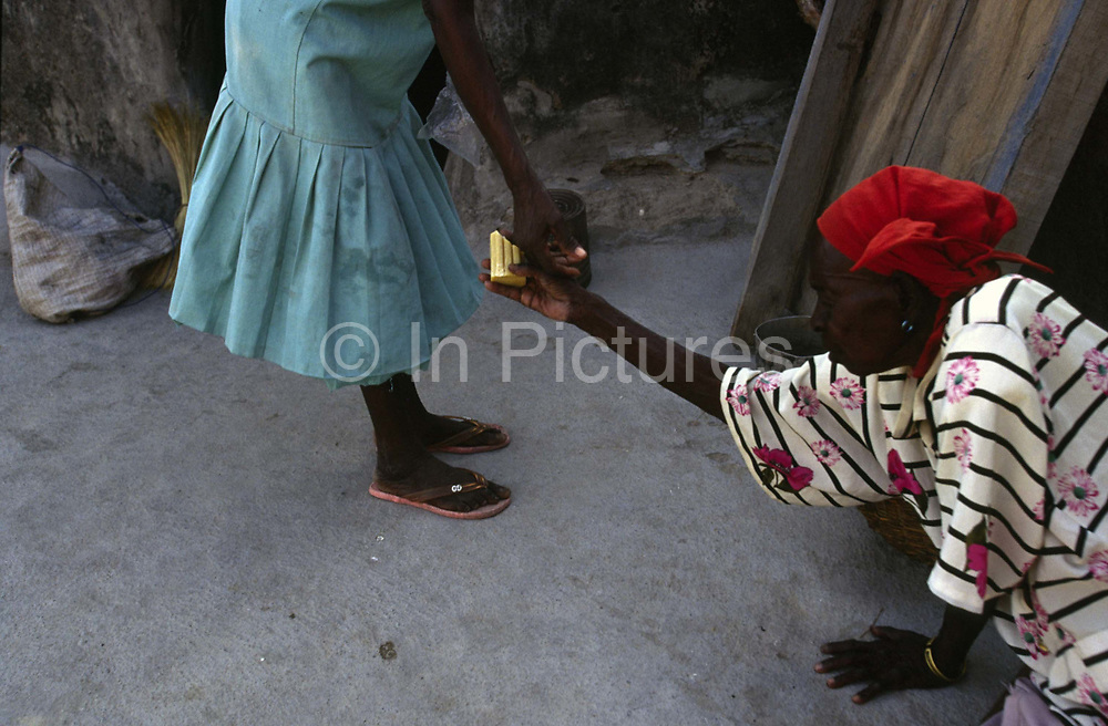 A blind neighbour holds a piece of soap to Asumpaheme who is also blind due to the entirely preventable 'River Blindness' (Onchocerciasis) Despite herhandicap, she has no choice but to continue farming.