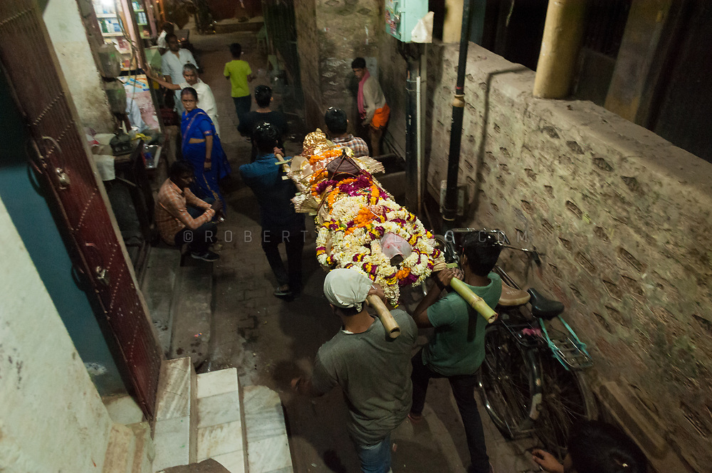 Men carry a decorated corpse to the cremation grounds in Varanasi, India. Photo © robertvansluis.com
