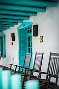 SHOT 12/29/15 4:03:18 PM - Rocking chairs on the front porch of the Taos Territorial Compound in Taos, N.M. Taos Territorial Compound is a luxury vacation lodging rental in Taos. Taos is a town in northern New Mexico's high desert, bounded by the Sangre de Cristo Mountains and incorporated in 1934 with a population of around 6,000. It's known for historic adobe buildings like Taos Pueblo, a multistory adobe complex inhabited by Native Americans for centuries. A longtime artist colony, Taos also offers many galleries and museums showcasing regional artwork (Photo by Marc Piscotty / © 2015)