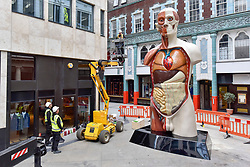 "© Licensed to London News Pictures. 24/06/2017. London, UK. Workmen unveil a 21 feet tall, 2.5 tonne bronze sculpture called ""Temple"" by Damien Hirst near the Lloyds Building in the City of London.  The artwork will be on display as part of ""Sculpture in the City"", a festival of sculpture in the City of London showing works by leading artists. Photo credit : Stephen Chung/LNP"